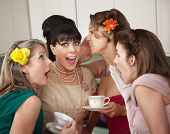 stock photo of foursome  - Group of four excited housewives in a kitchen share secrets - JPG