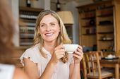 Mature woman holding coffee cup and talking with her friend. Beautiful woman smiling and sitting at  poster
