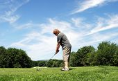 stock photo of pro-life  - Man prepares to hit a golf ball on the course - JPG
