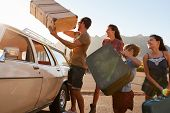 Family Loading Luggage Onto Car Roof Rack Ready For Road Trip poster