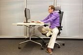 sitting position at workstation. man on chair working with computer stretching leg poster