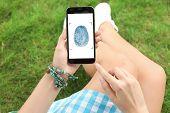 Woman Holding Mobile Phone With Fingerprint Sensor Outdoors, Closeup poster