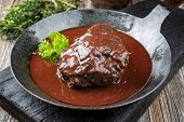 Traditional German braised beef cheeks in brown red wine sauce with herbs as closeup in a wrought-ir poster