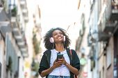 Beautiful Afro American Girl Listening Music On Headphones Outdoors. poster