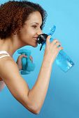 pic of drinking water  - Athlete taking a break at the gym for a quick drink from her water bottle - JPG