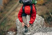 Caucasian Young Hiker Man Hiking In Mountains Dressed In Red Clothes Exploring New Places. Traveler  poster