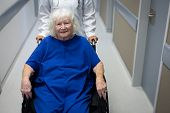 Portrait of a senior Caucasian female patient sitting in a wheelchair and looking at the camera whi poster