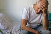 Front view of frustrated senior Caucasian  male patient sitting on bed at retirement home. He touche poster