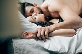 Selective Focus Of Passionate Man Holding Hands With Woman While Lying On Bed poster