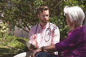 Side view of a confident Caucasian male doctor showing medical reports to senior Caucasian woman at  poster