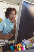 Front view of young thoughtful mixed race male graphic designer with hand on chin looking at compute poster