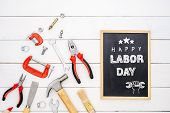 Happy Labor Day Background Concept. Flat Lay Of Construction Handy Tools With Black Chalkboard With  poster