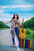Hitchhiking girl. Beautiful hippie girl standing on a highway and catching a passing car. Spirit of  poster