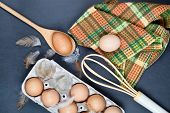 Eggs, baking ingredients and feathes on backboard background. Eggs, wooden spoon, whisker, towel and poster