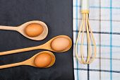 Eggs and kitchen utensil on backboard background. Eggs, wooden spoon, whisker, towel and other cooki poster
