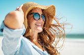 Side view of beautiful mature woman wearing sunglasses at beach. Young smiling woman on vacation loo poster