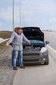 Desperate Young Man With A Broken Car On The Highway. poster