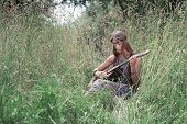 Young Hippie Woman Playing Guitar Sitting On Forest Glade poster