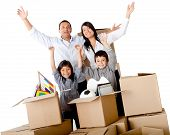 Family excited moving house packing in cardboard boxes â?? isolated