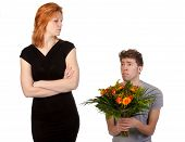 Young Boy Offering A Bunch Of Flowers To His Angry Girlfriend