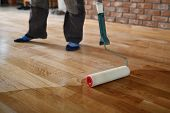 Lacquering Wood Floors. Worker Uses A Roller To Coating Floors. Varnishing Lacquering Parquet Floor  poster