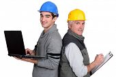 senior plumber and junior standing back to back with laptop and clipboard