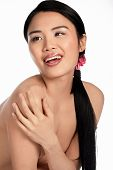 Beautiful sexy topless Asian woman with her arm covering her breasts laughing and looking teasingly over her shoulder isolated on white