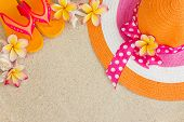 Hat And Flip Flops In The Sand With Shells And Frangipani Flowers. Summertime On Beach Concept..