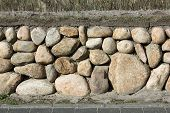 stock photo of fieldstone-wall  - The Frisian stone wall is a dry stone wall typical for Northern On the top is a layer of soil who is planted in different ways - JPG
