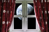Planet viewed through a window with curtains