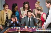 Man winning as another is losing at roulette table in casino