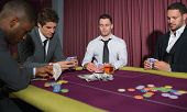 Men playing high stakes game of poker in casino