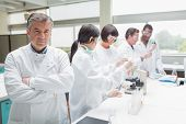 Chemist standing with arms folded in busy lab