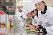 pic of supervision  - Happy chef looking up from preparing salad in culinary class - JPG