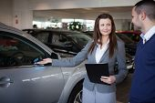Woman presenting something to a man in a dealership