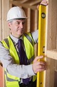 Man with warning vest and helmet measuring wooden frame with spirit level