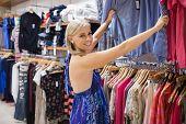 Frau suchen durch Kleider und lächelnd in Einkaufszentrum