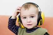 Young Child On Couch With Earmuffs