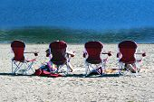 People Relaxing And Sunbathing In A Row Of Beach Chairs On The Sand In Front Of The Ocean
