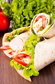 stock photo of sandwich wrap  - Fresh tortilla wrap sandwiches with vegetables and turkey - JPG