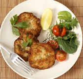 Easy to make fishcakes, with steamed fish crumbled into mashed potato and parsley mix, thickened with some flour, rolled in breadcrumbs and fried, served with a salad. High angle view