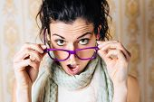picture of jaw drop  - Surprised woman looking over her glasses - JPG