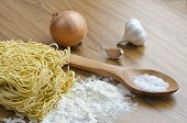 foto of egg noodles  - Three eggs and dry egg noodles on the kitchen table and a napkin with a wooden spoon. Ingredients for cooking noodles.