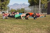 image of lady boots  - Boot camp fitness group doing push up exercises outdoors - JPG