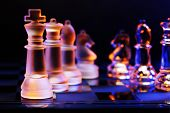 image of chessboard  - Glass chess on a chessboard lit by a colorful blue and orange light and placed on a glass chessboard - JPG