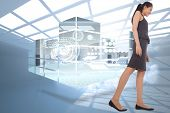 Asian businesswoman walking against room with holographic cloud