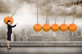 image of newton  - Serious businesswoman pointing against newtons cradle above city - JPG