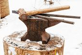 image of tong  - anvil with blacksmith tongs and hammer in old abandoned village smithy in winter