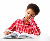 foto of pre-teen boy  - Bored African American school boy reading book without interest education and school concept - JPG