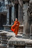 Angkor, Cambodia - January 1, 2014: buddhist monk walking in angkor wat temple
